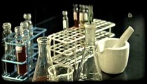 Man mixes chemicals in lab. Vintage stylized video clip.