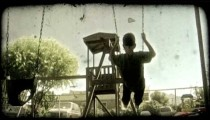 Boy swings at playground. Vintage stylized video clip.