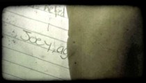 Young boy finishes letter. Vintage stylized video clip.