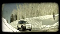 SUV drives down hill. Vintage stylized video clip.
