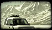 SUV near mountains. Vintage stylized video clip.