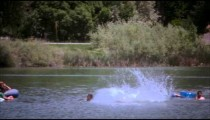 Panning, slow motion shot of a boy riding his bike off a dock and into a lake.