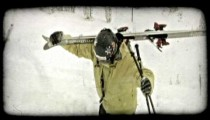 Skier carries skis up powdery hill. Vintage stylized video clip.