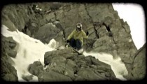 Expert skier jumps off rocky hill. Vintage stylized video clip.