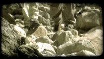 Couple hikes over rocks. Vintage stylized video clip.