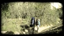 Couple hikes in mountains. Vintage stylized video clip.