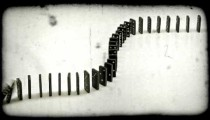 Shot of dominoes toppling on top of each other. Vintage stylized video clip.
