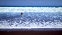 Long distance static shot of woman playing in the water near the beach