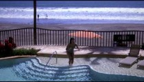Slow motion, panning shot of woman diving into a pool.