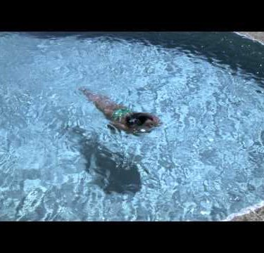Slow motion shot looking down at a woman swimming in a pool.