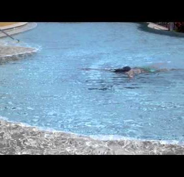 Slow motion of woman swimming underwater in a pool.
