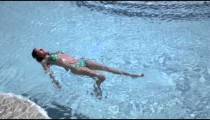 Panning, slow motion shot of beach to woman swimming in a pool.