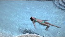 Slow motion shot of a woman doing a backstoke in a pool.