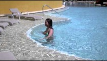 Slow motion shot of a woman moving towards the edge of a pool.