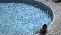 Slow motion shot of a girl leaning against the side of a pool.