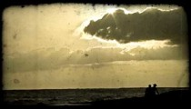 People on beach at sunset. Vintage stylized video clip.
