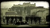 Tour group below castle. Vintage stylized video clip.