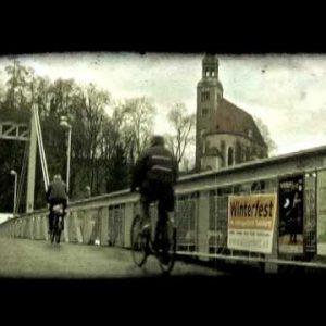 Two bike riders cross bridge. Vintage stylized video clip.