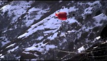 Shot of base jumper landing in snow with open parachute.