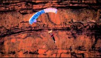 Slow motion shot of base jumper descending with open parachute.