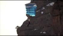 Slow-motion shot of base jumper going in for landing.