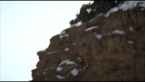 Slow motion shot of base jumper skiing down a hill then doing three back flips in the air.
