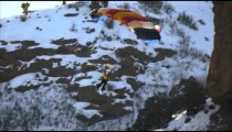 A base jumper descending a rocky mountainside in slow motion.