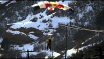 A base jumper descending then landing on snowy road. Shot in slow motion.