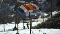 Slow motion shot of base jumper landing on snowy mountain road.