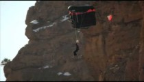 Shot of man skiing down slope, base jumping, somersaulting, descending and landing in slow motion.