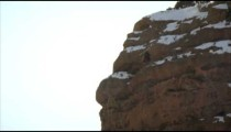 Slow motion shot of base jumper skiing off cliff and somersaulting in the air.