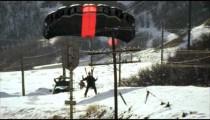 slow motion shot of a base jumper landing on a ski slope, wearing skis.