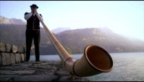 Low-angle footage of man playing alphorn next to lake