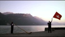 Man flourishes and throws Swiss flag while standing near alphorn player
