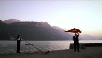 Man twirls and tosses Swiss flag while standing near alphorn player
