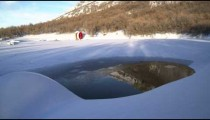 Time lapse of red water wheel on edge of snow-covered frozen lake and hill