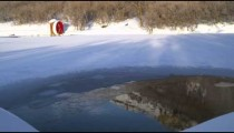 Red water wheel on edge of snow-covered frozen lake and hill