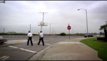 Slow motion footage of two men crossing a street at LAX