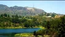 Static shot of reservoir, hills bearing Hollywood sign, houses