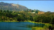 Pan of reservoir, hills bearing Hollywood sign, houses