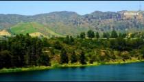 Pan of reservoir, hills around Hollywood sign