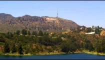 Long distance static shot of the Hollywood sign with a body of water in the foreground