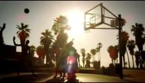 Lens flare shot of basketball game near Venice Beach, California filmed at varying speeds