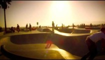 Slow motion shot of a skater jumping over a ramp in skate park near Venice Beach, California