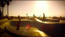 Slow motion shot of skateboarder and rollerblader in skate park near Venice Beach, California