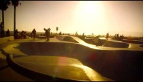 Slow motion lens flare shot of skateboarders on ramp near Venice Beach, California