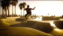 Slow motion lens flare shot of a skateboarder jumping over a ramp near Venice Beach, California