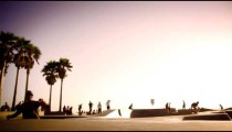 Slow motion shot of jumping skateboarder at Ocean Front Walk near Venice Beach, California