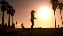 Slow motion shot with lens flare of a woman playing with a hula hoop near Venice Beach, California