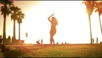 Hula hoop performance of women filmed in slow motion with lens flare near Venice Beach, California